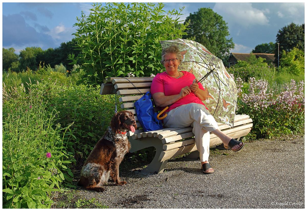 dame met hond en parasol zittend op bankje in de tuin