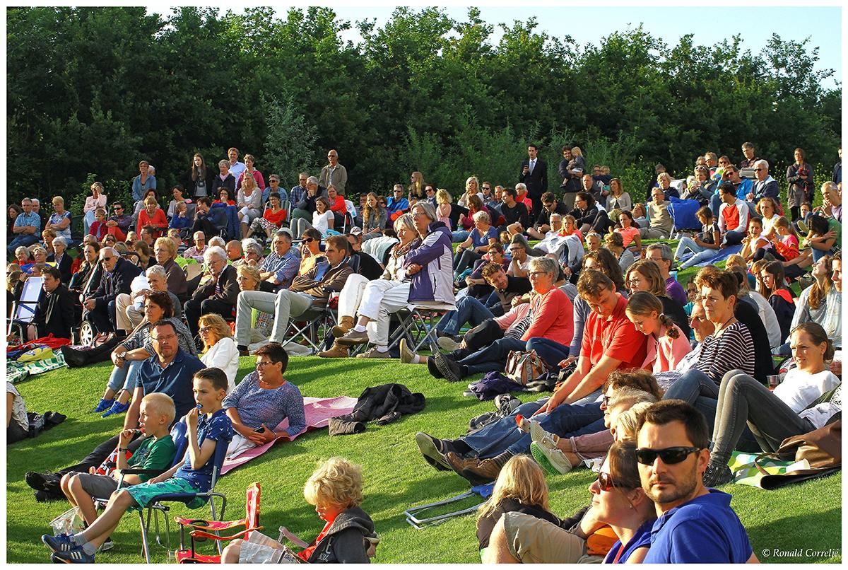 publiek zittend op heuvel