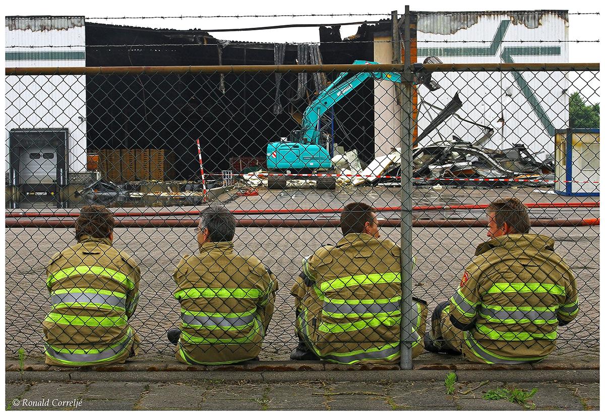 brandweerlieden rusten uit tegen hek