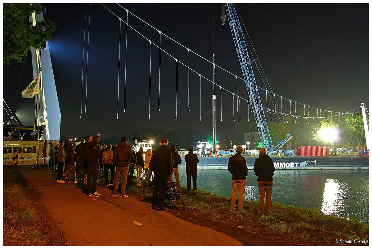 Toeschouwers bij het bouwen van een brug in de nacht
