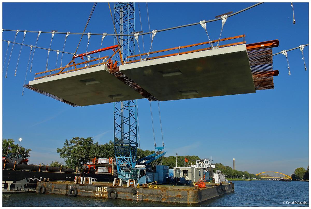 Dek van een brug hangend in hijskraan boven water