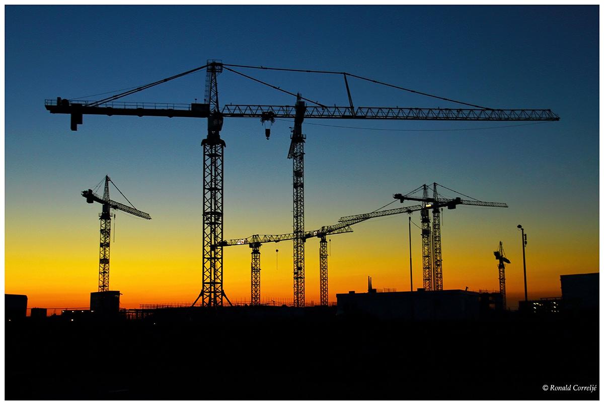 zonsondergang met bouwkranen
