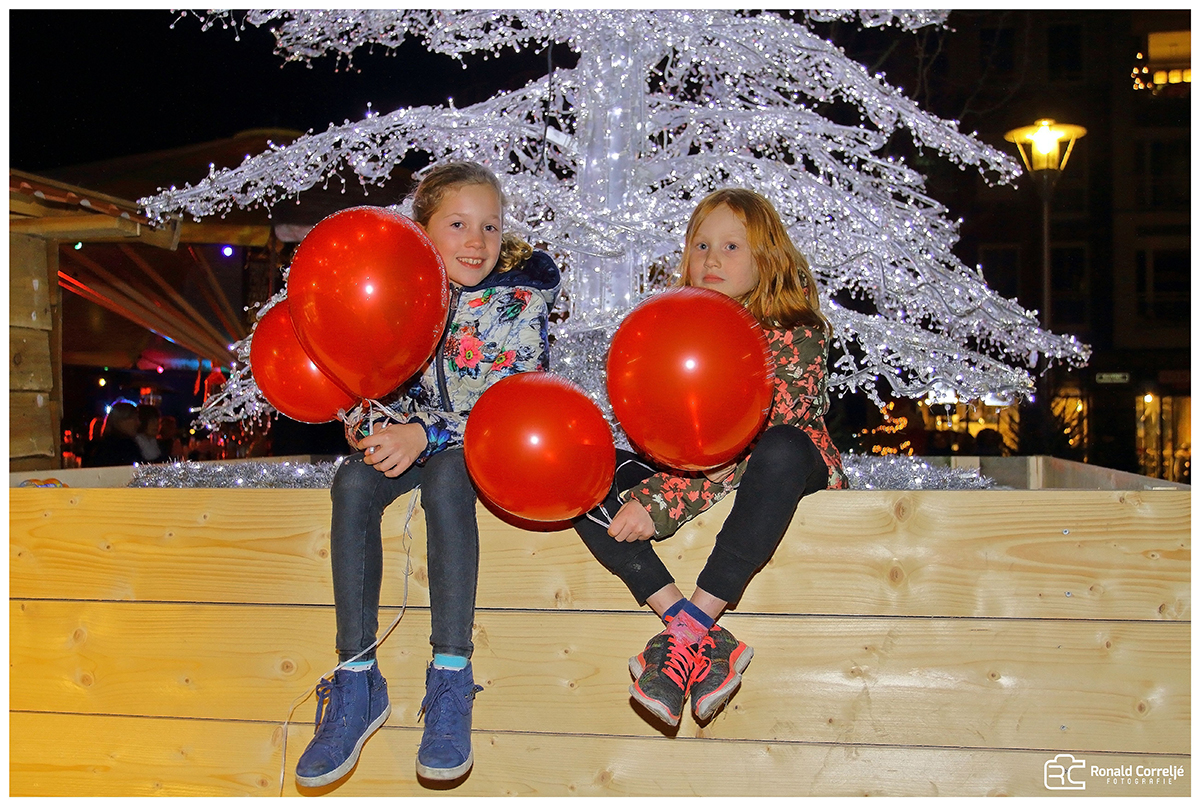 twee meisjes zittend op een bank met ballonnen