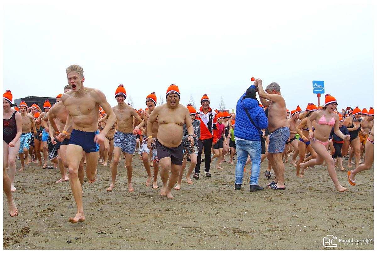 zwemmers lopen op het strand naar het water