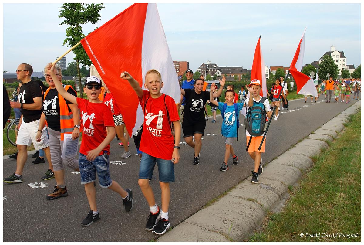 wandelaars avondvierdaagse met vlaggen
