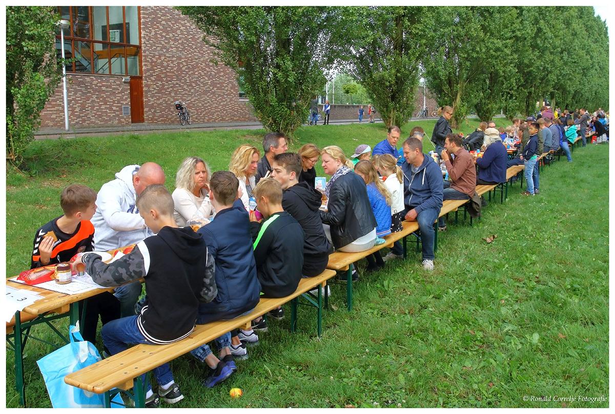 veel mensen zittend aan een lange ontbijttafel in de buitenlucht