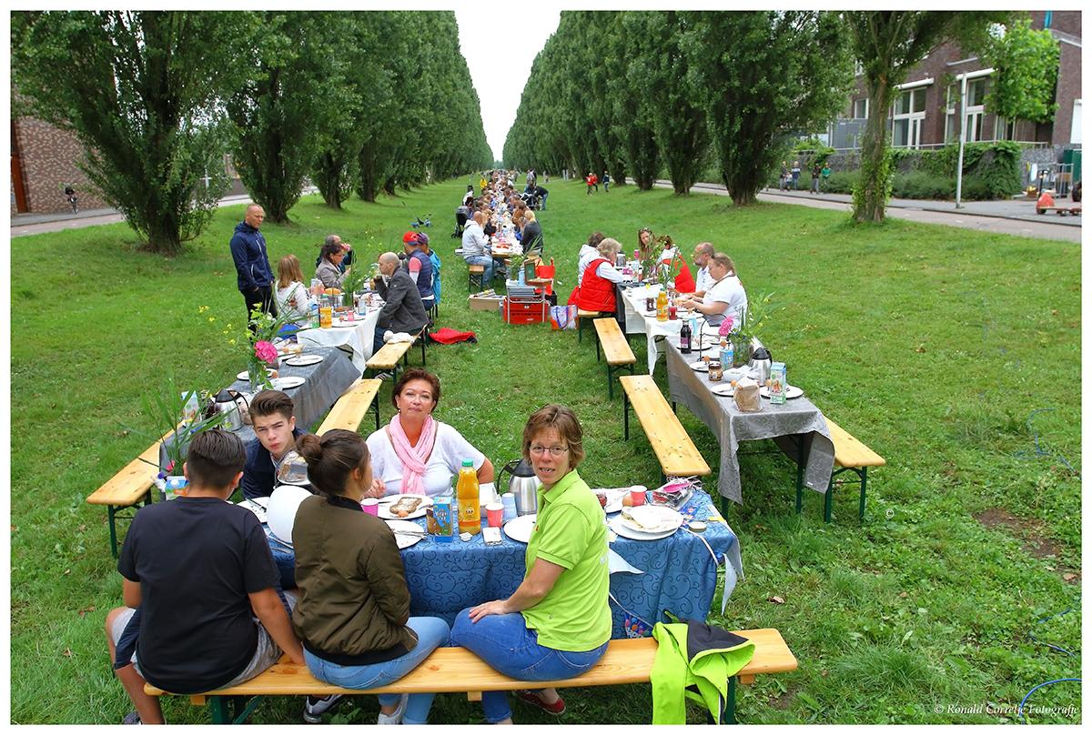 groot ontbijt met veel mensen in de buitenlucht