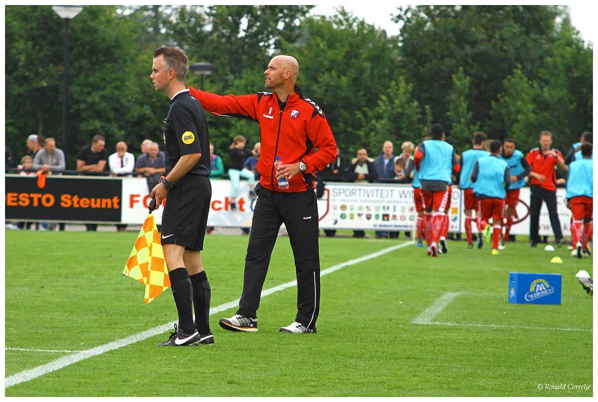 trainer en scheidsrechter bij voetbalwedstrijd