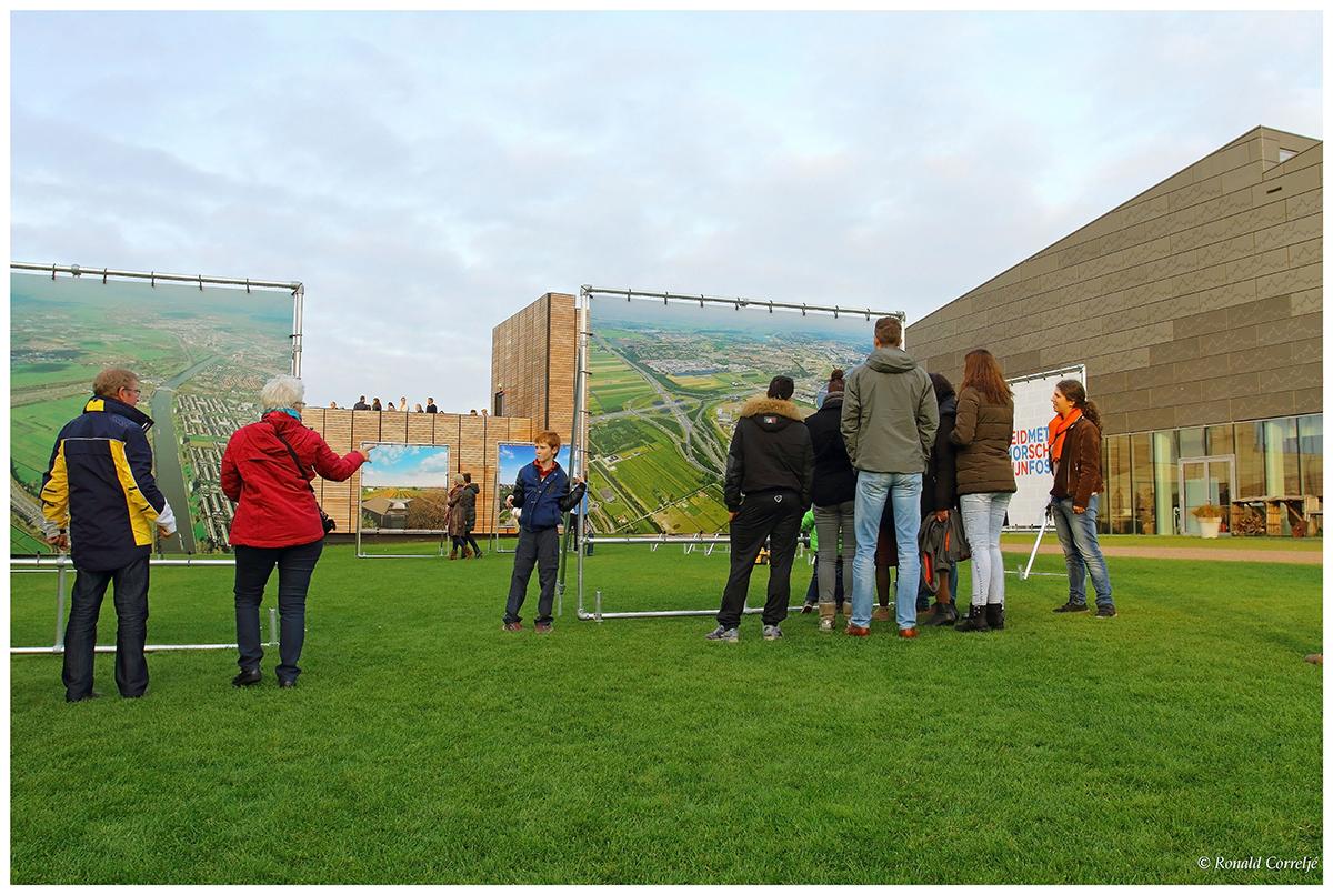 personen op grasveld kijkend naar een tentoonstelling