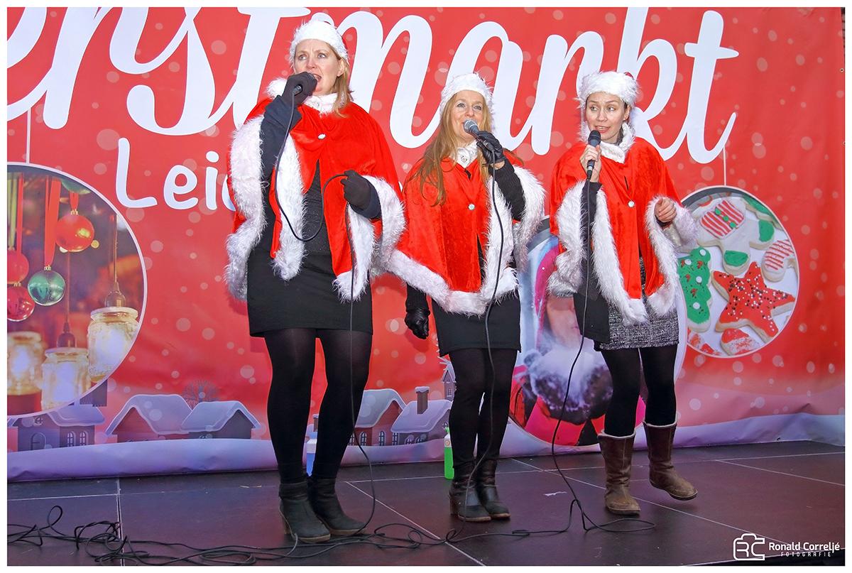 drie zangeressen verkleed als kerstman