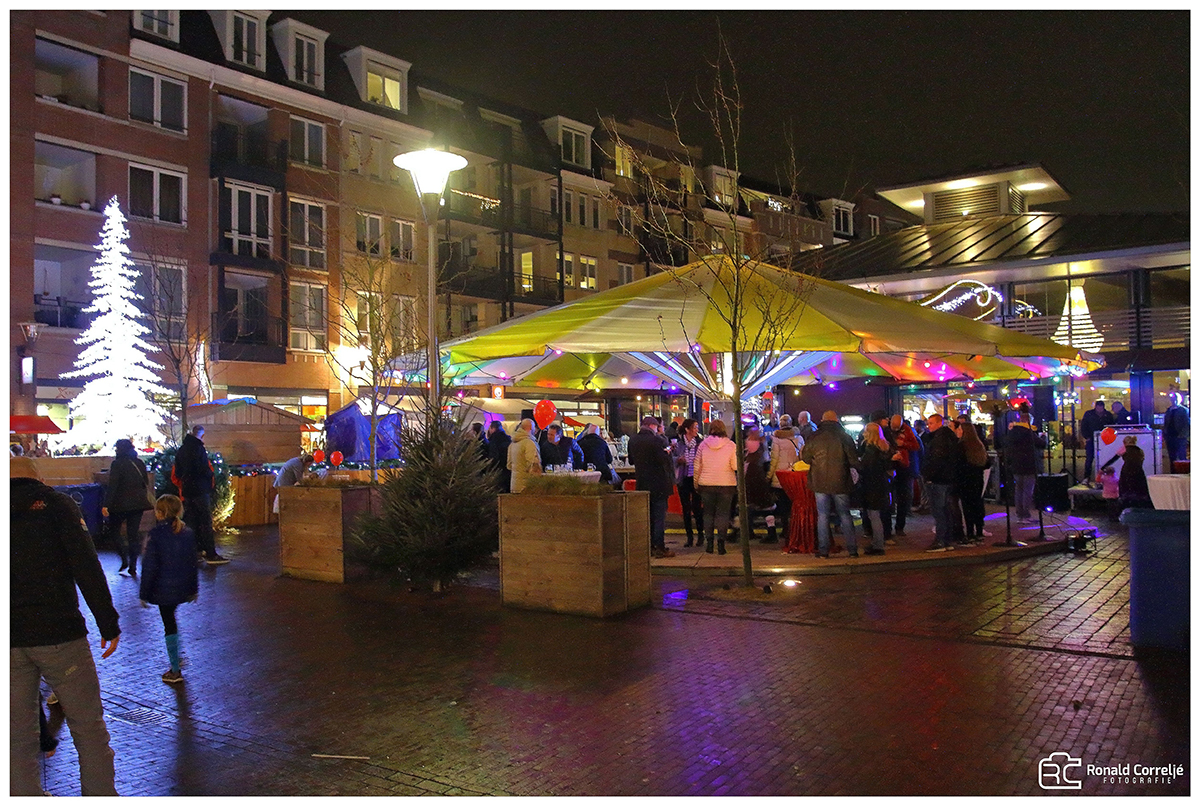 mensen onder grote parasol op kerstmarkt