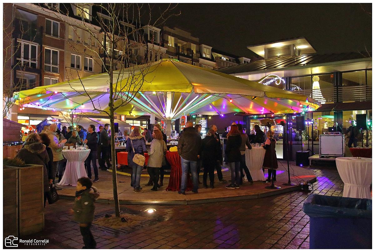mensen onder een parasol op kerstmarkt bij avond