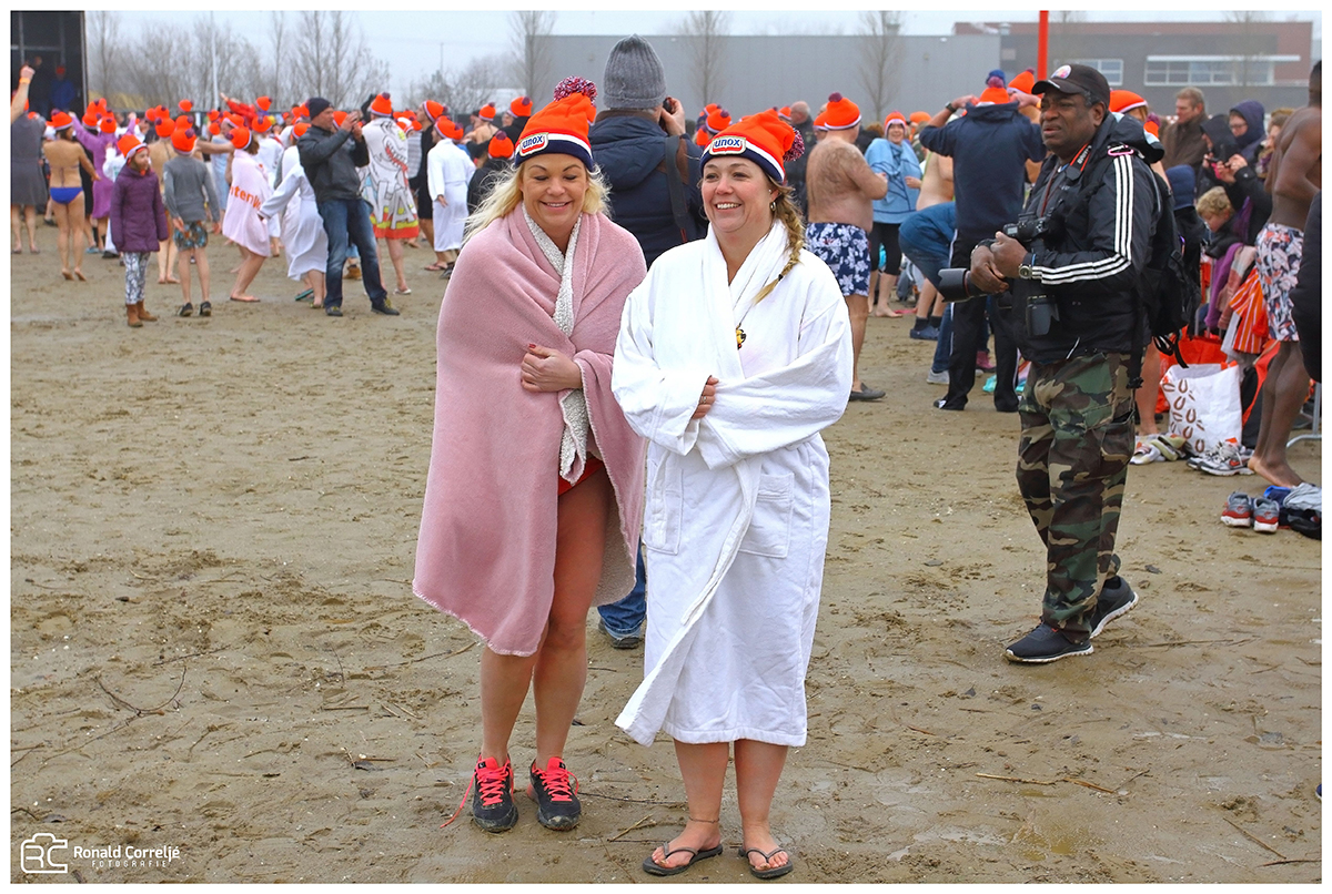 twee dames in badjassen op het ijskoude strand