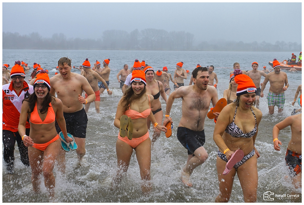 zwemmers met mutsen op in ijskoud water