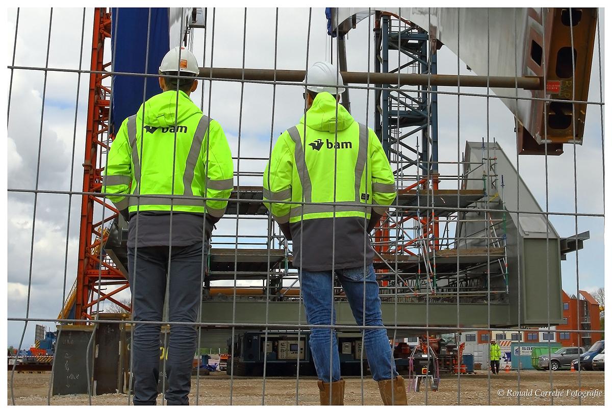 toeschouwers kijken naar de bouw van een stalen brug