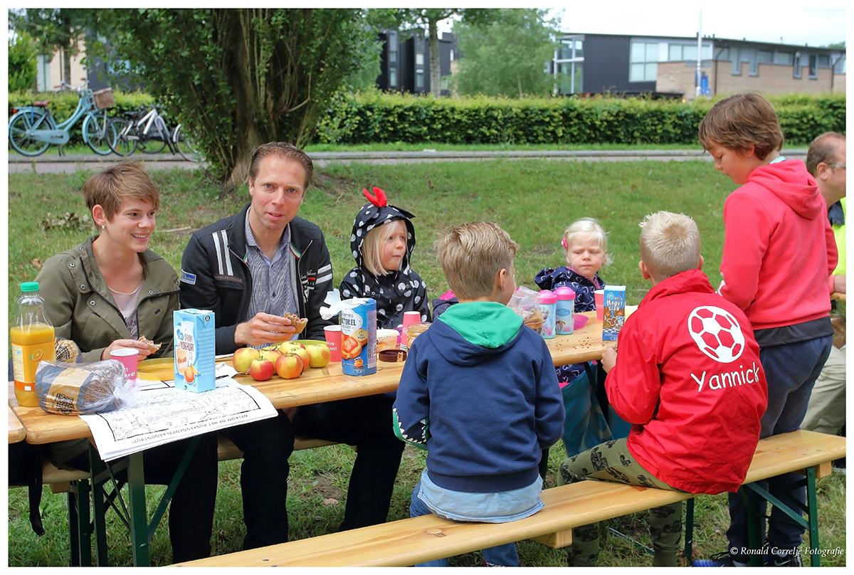 gezin zittend aan ontbijttafel in de buitenlucht